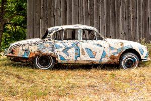 Verbeulter und versprayter Jaguar als Kunstobjekt